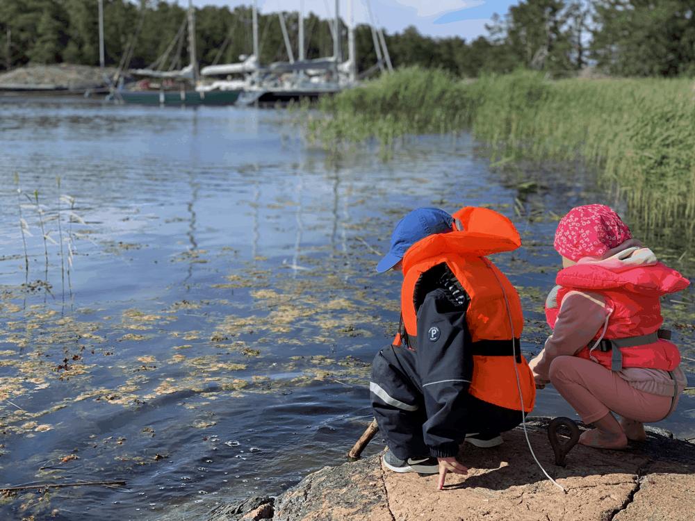 Kaksi lasta veden äärellä pelastusliiveissä
