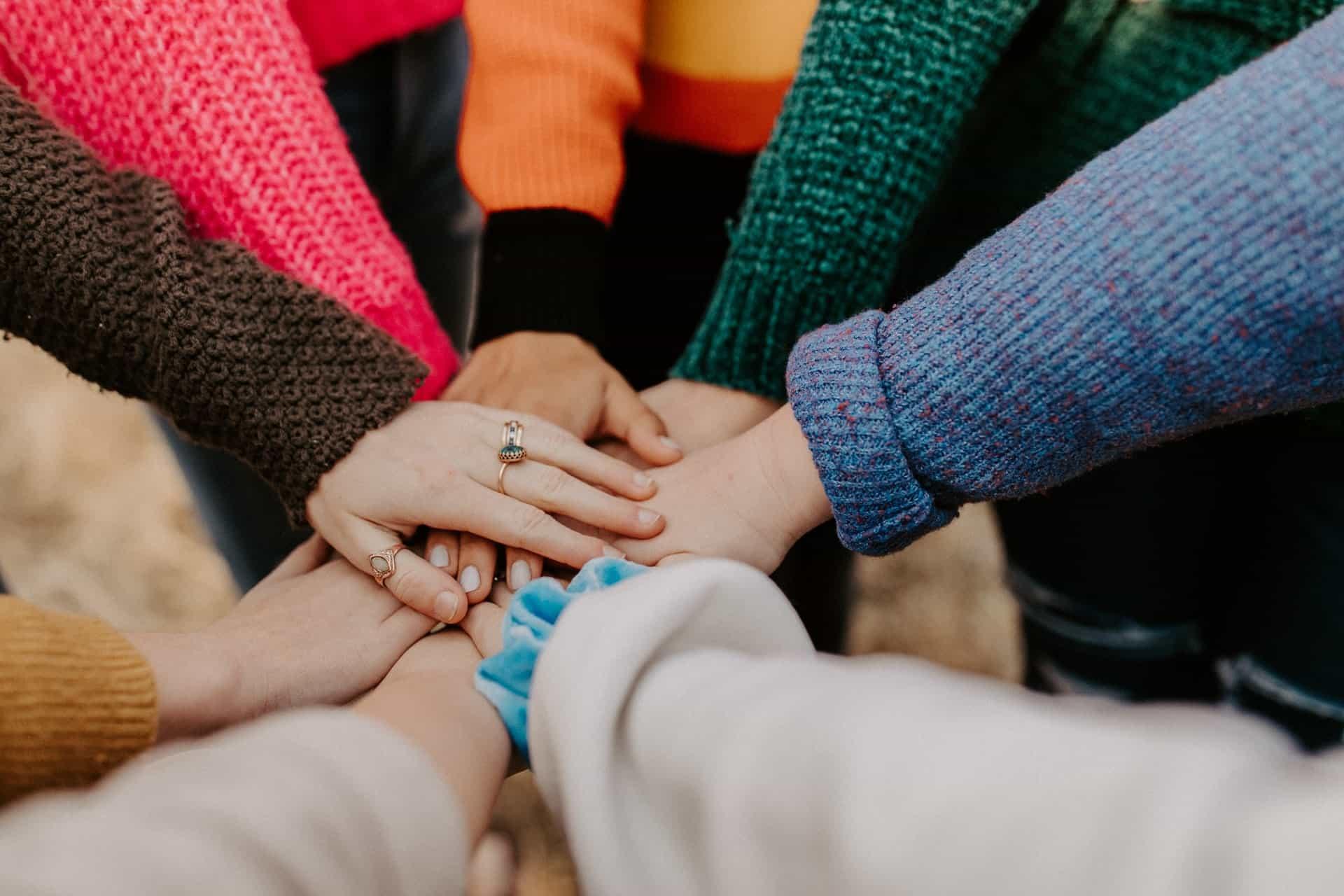 Ryhmä ihmisiä on asettanut kätensä päällekkäin.