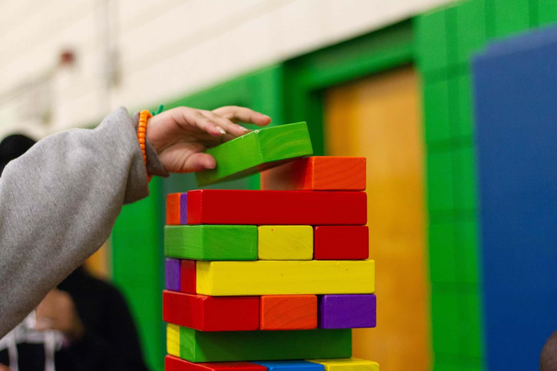 Lapsi tekee tornia eri värisistä rakennuspalikoista.